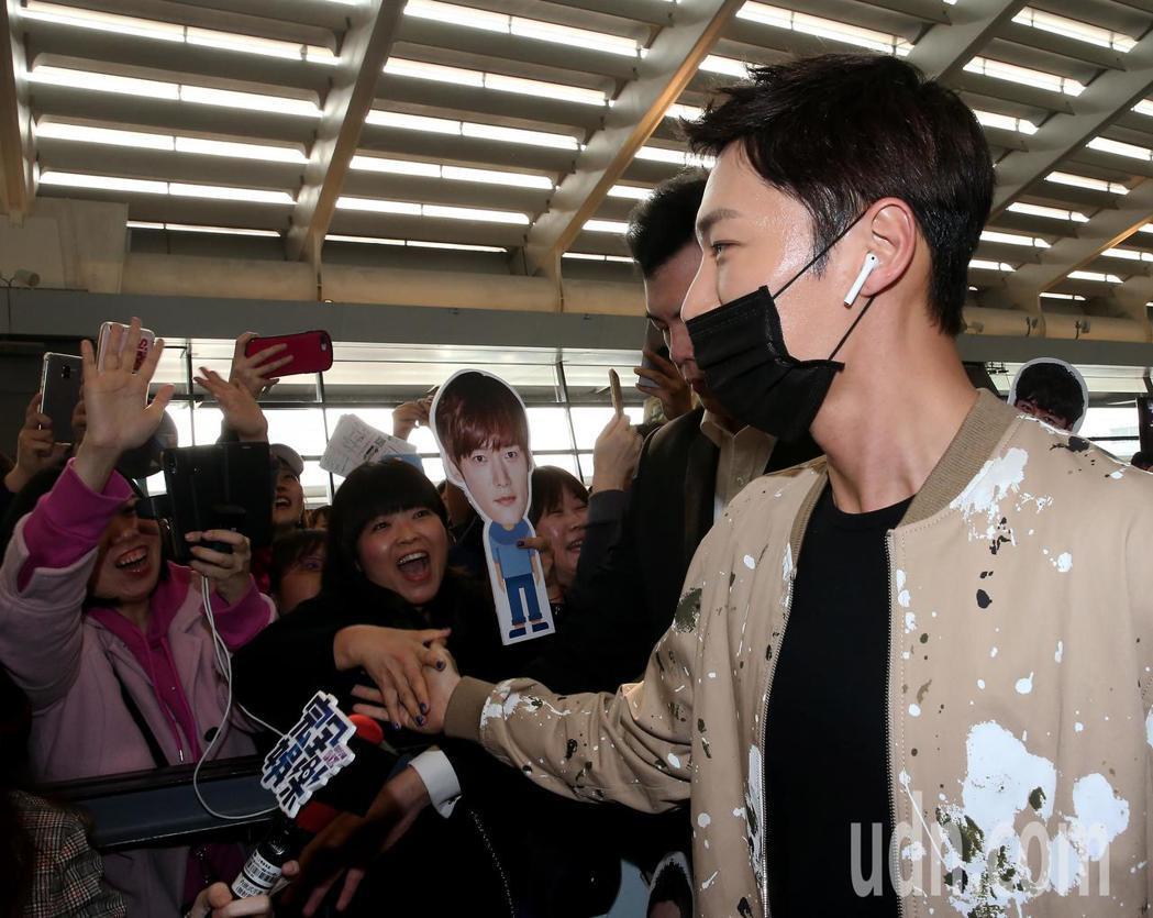 南韓藝人崔振赫(右)27日下午搭機抵達桃園機場,粉絲擠爆桃園機場入境大廳接機。記...