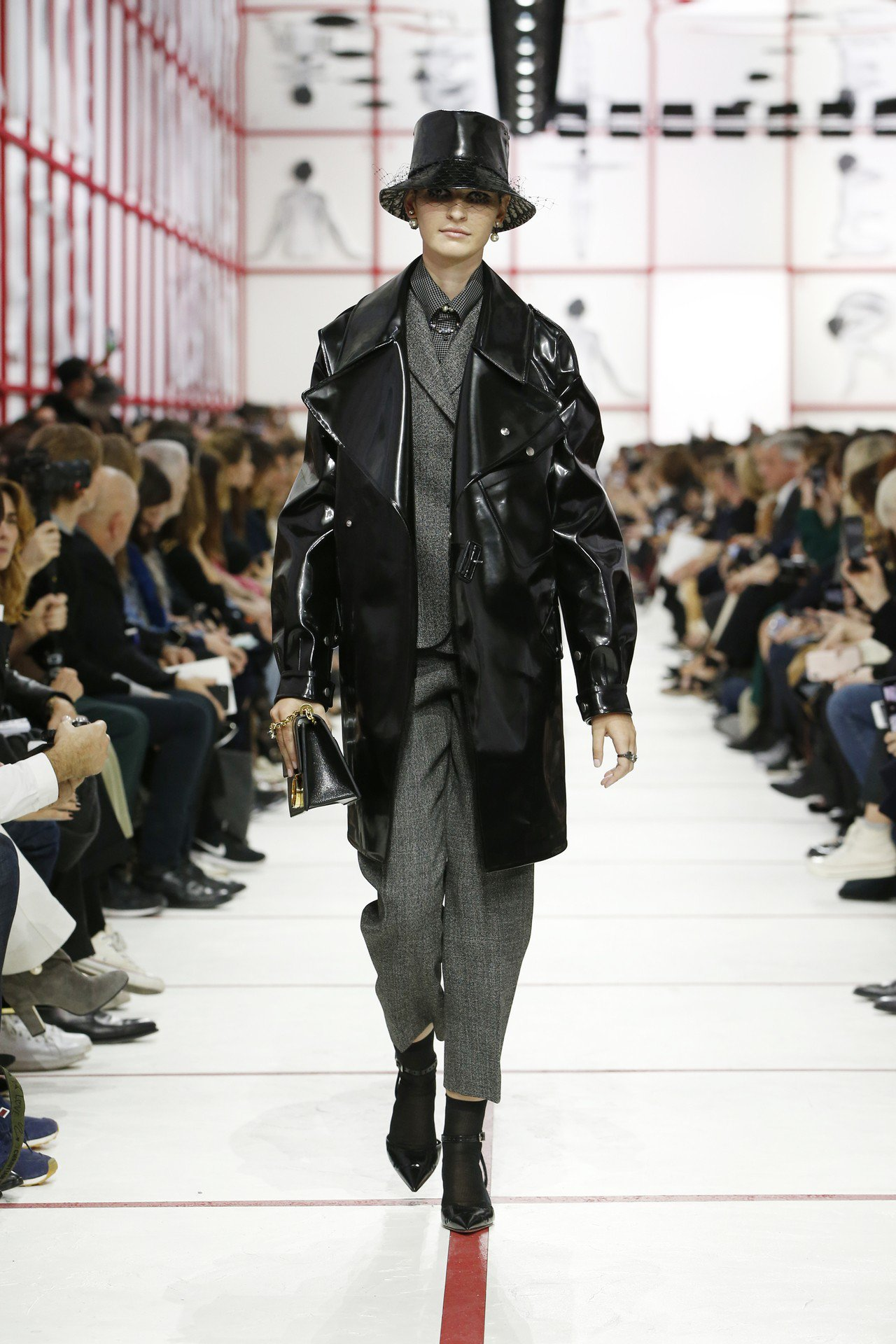 長版的黑色亮面皮革外套也是向50、60年代地下文化汲取靈感的設計。圖/Dior提...