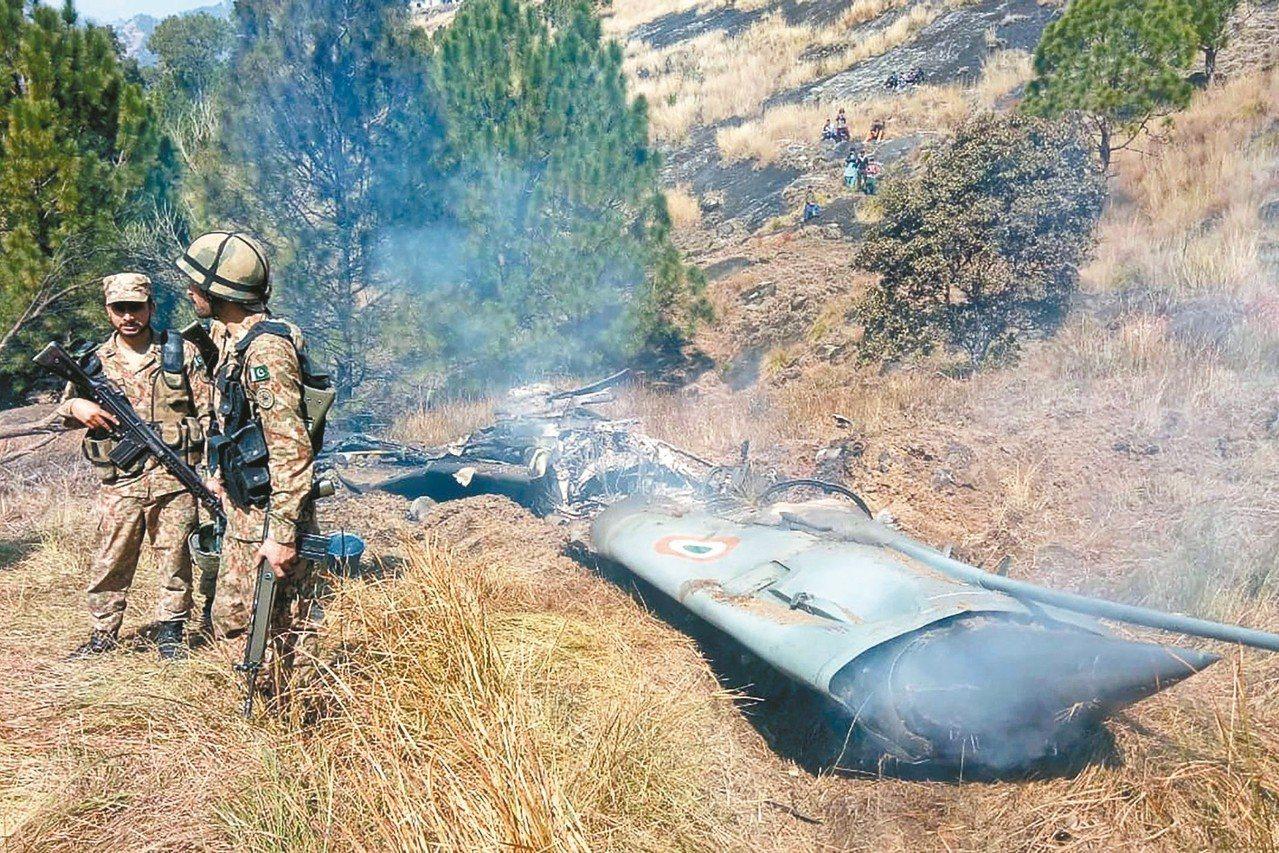 巴基斯坦軍人廿七日在巴屬克什米爾看守遭擊落的印度戰機殘骸。 (法新社)
