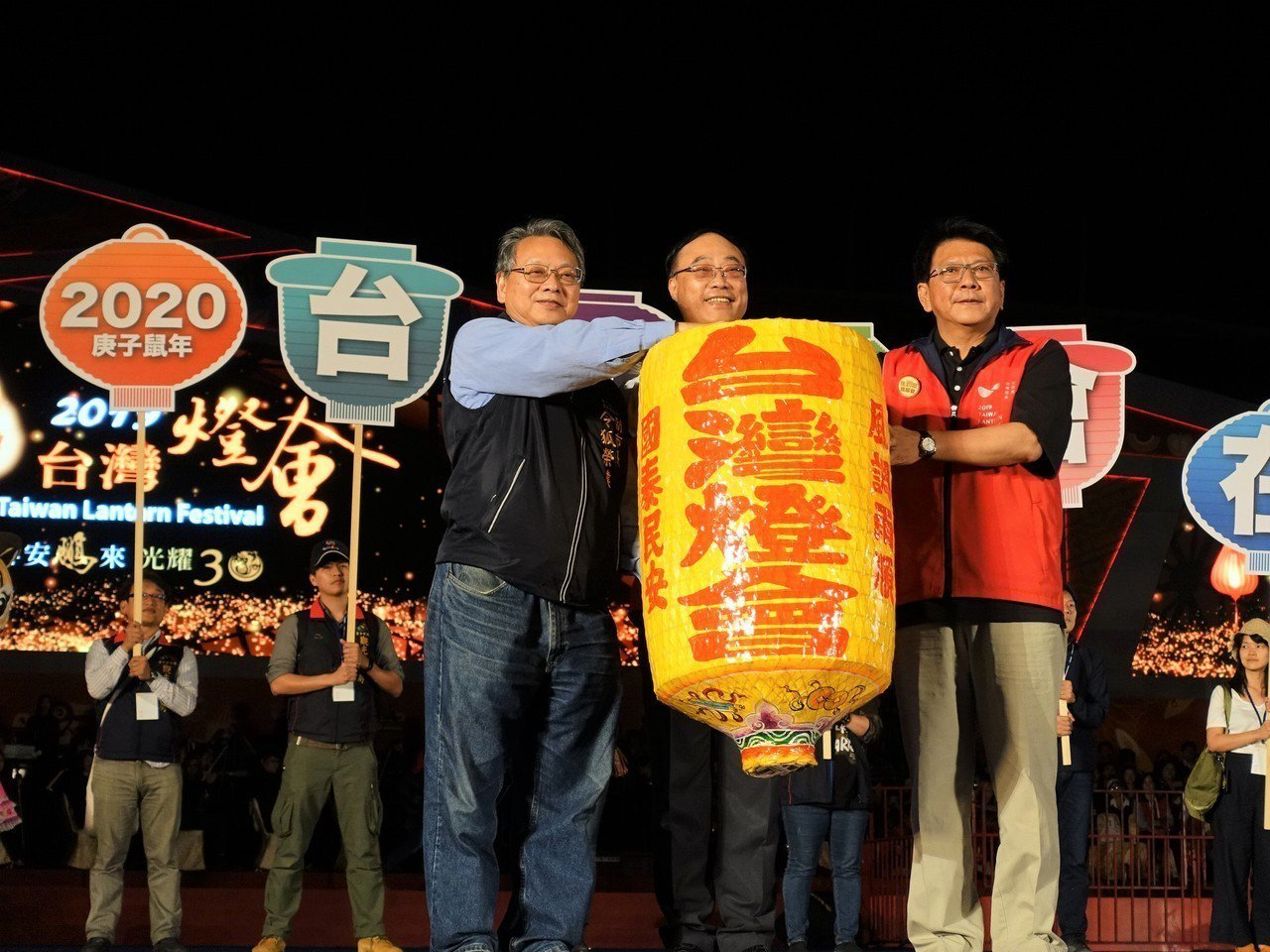 交通部觀光局長周永暉(中)、屏東縣長潘孟安(右)今晚把象徵2020燈會主辦權的傳...