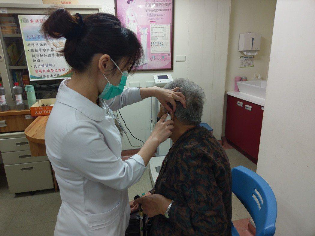 衛生福利部豐原醫院護理人員為患者量體溫。圖/衛福部豐原醫院提供