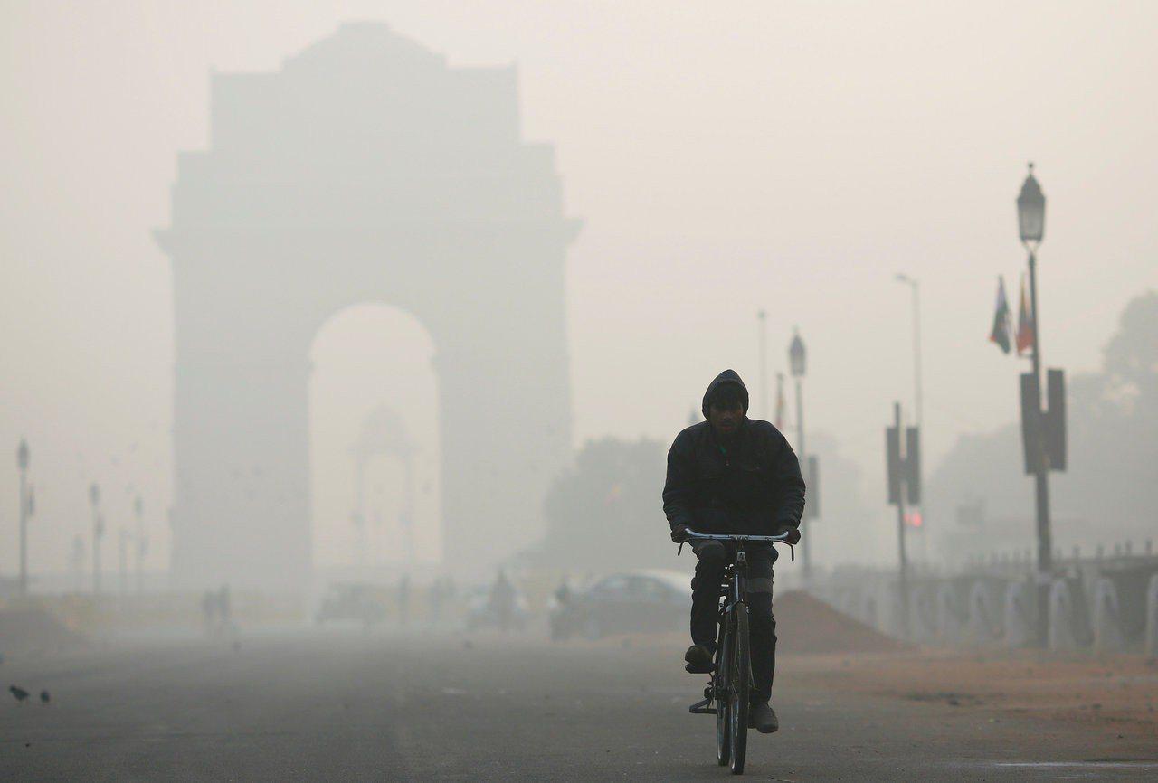 印度空氣汙染嚴重,一名男子在首都新德里國王大道騎自行車,後方的獨立紀念碑「印度門...