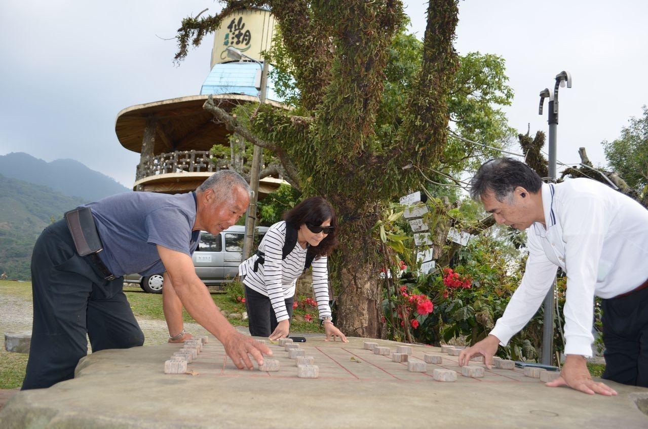 吳森富董事長(左)與遊客一起玩大象棋。  陳慧明 攝影