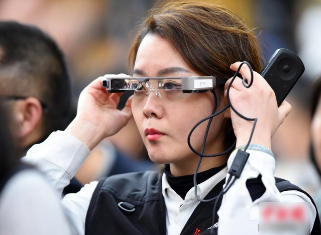 有女記者戴上一款價值699美元Epson的智能眼鏡,拍攝現場畫面。(中新網)