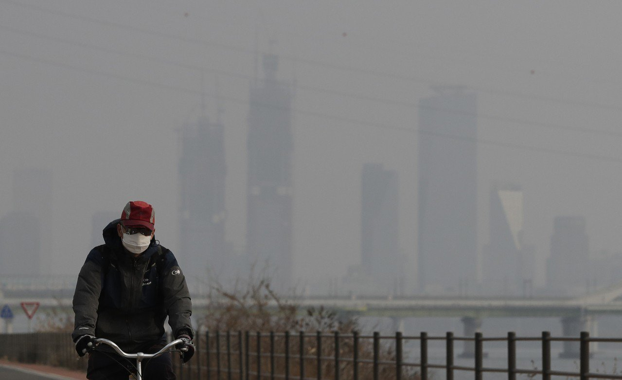 首爾空汙嚴重,一名男子六日帶著口罩在漢江旁騎車。(美聯社)