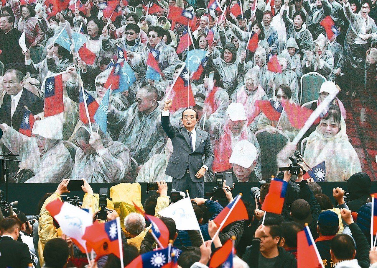 王金平在200多位民眾簇擁下上台,象徵自己與百工百業站在一起,現場民眾揮舞國旗高...