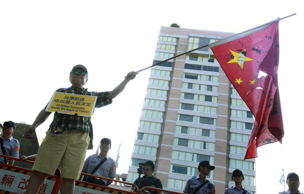 一名民眾揮舞五星旗,訴求「台灣前途由台灣人民決定」。 圖/美聯社