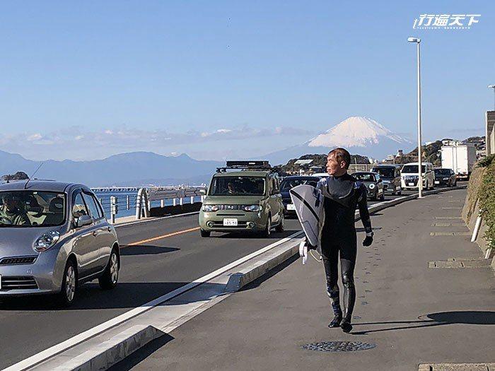 拿著浪板以富士山當背景的玩家,是湘南海岸常見的風景。