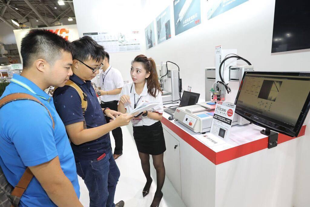 產品經理蔡易婷(右)向參觀來賓介紹多功能桌上型機械手「JTB Series」。東...