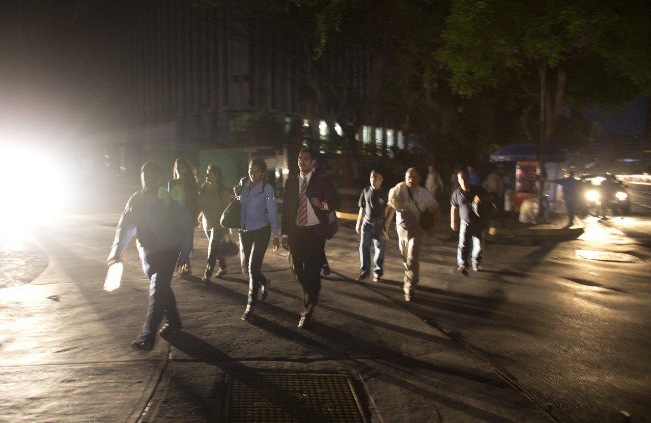 委內瑞拉首都卡拉卡斯,民眾走在停電的黑暗街上。 美聯社