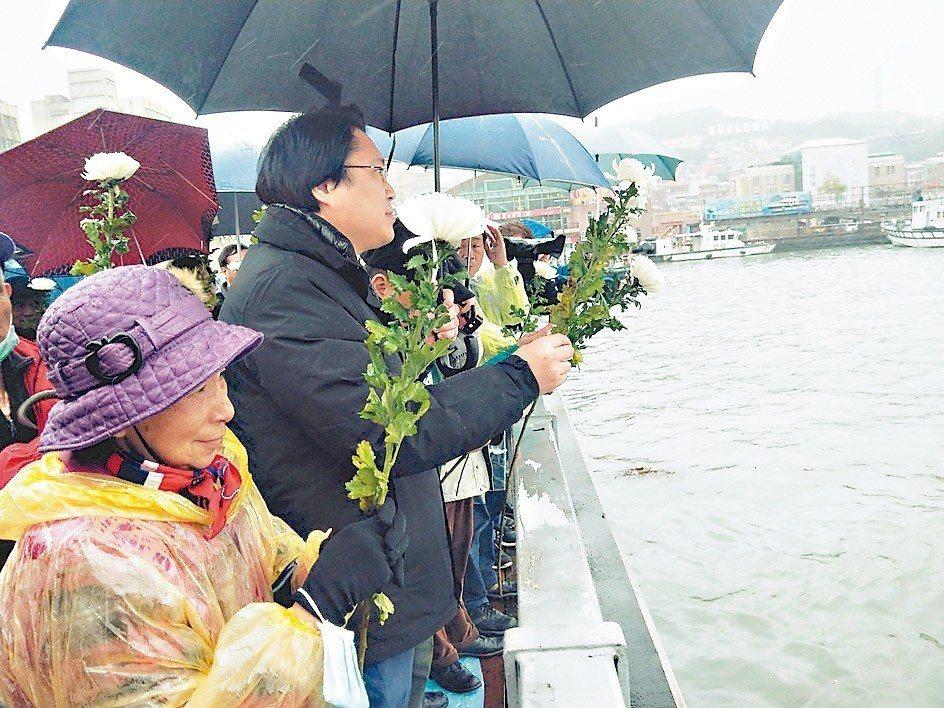 基隆市政府昨在海洋廣場舉辦228紀念追思活動,市長林右昌(左二)與受難者家屬把花...