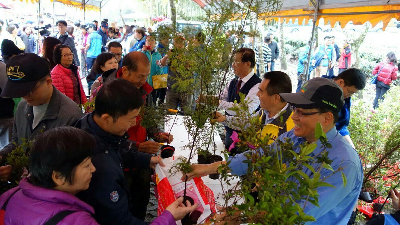 南投林管處今天在瑞龍瀑布舉辦植樹活動,並贈送台灣肖楠等樹苗,許多民眾排隊領取。圖...