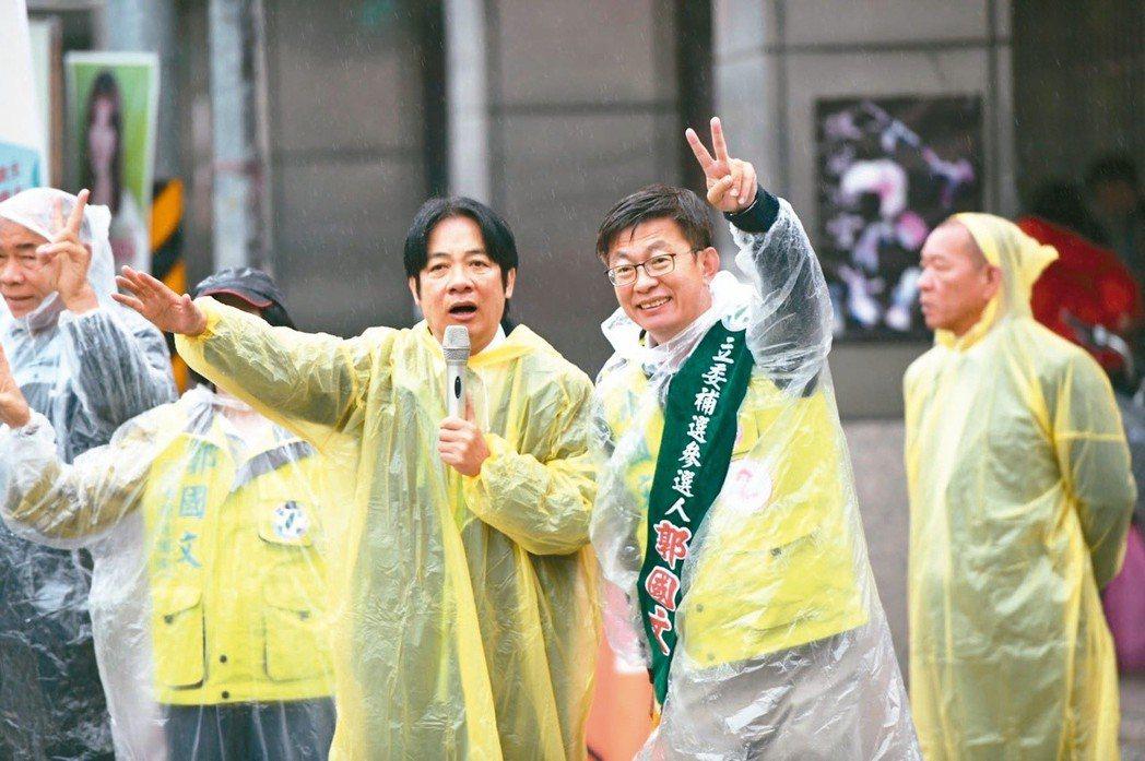 行政院前院長賴清德(左)賣力輔選郭國文(右),連下雨天都穿著雨衣站在路口拜票。 ...