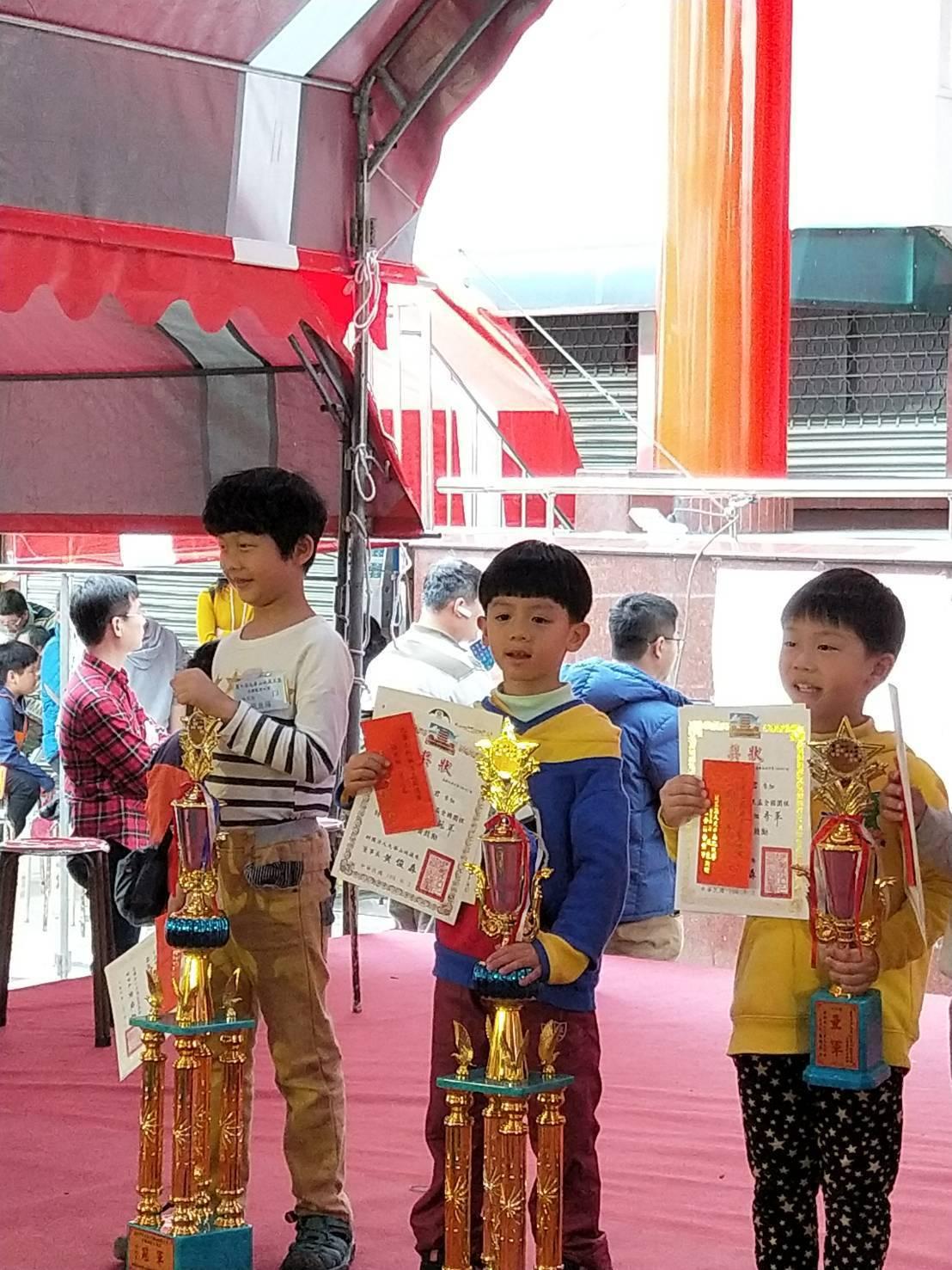 6歲的洪睿辰(中)一路過關斬將,得到幼兒組冠軍,讓陪同參賽的爺爺、爸媽感到欣慰。...