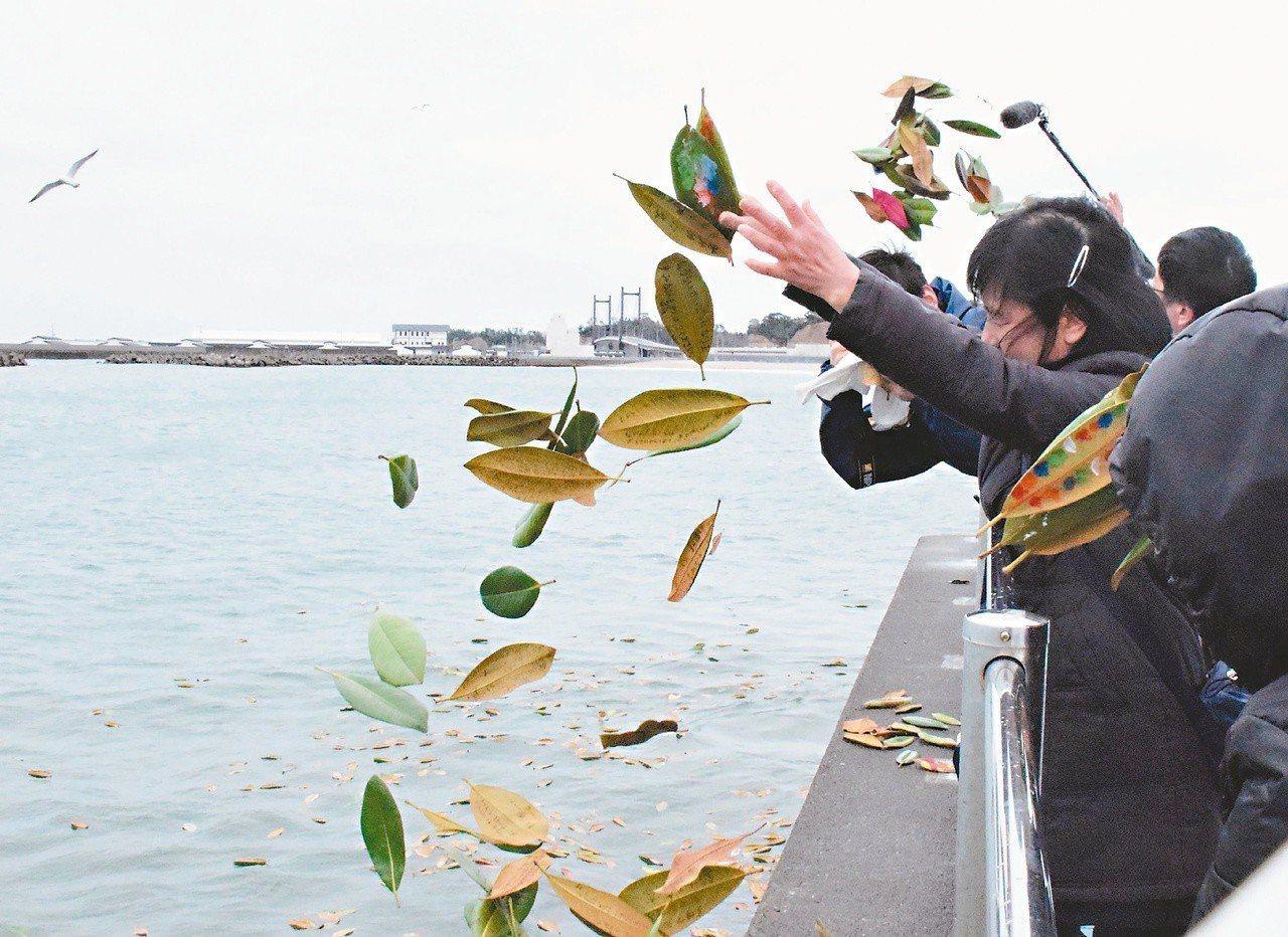 日本民眾十一日在福島縣相馬市朝海中灑樹葉,悼念三一一地震海嘯罹難者。(法新社)
