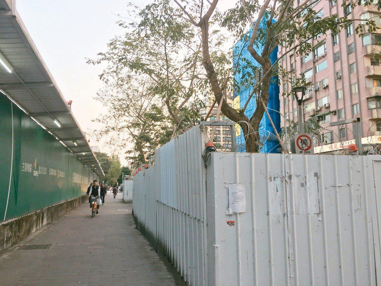 大巨蛋光復南路、忠孝東路側的33棵樹,已圍上鐵皮,為防抗議人士,上方還有刀片刺網...