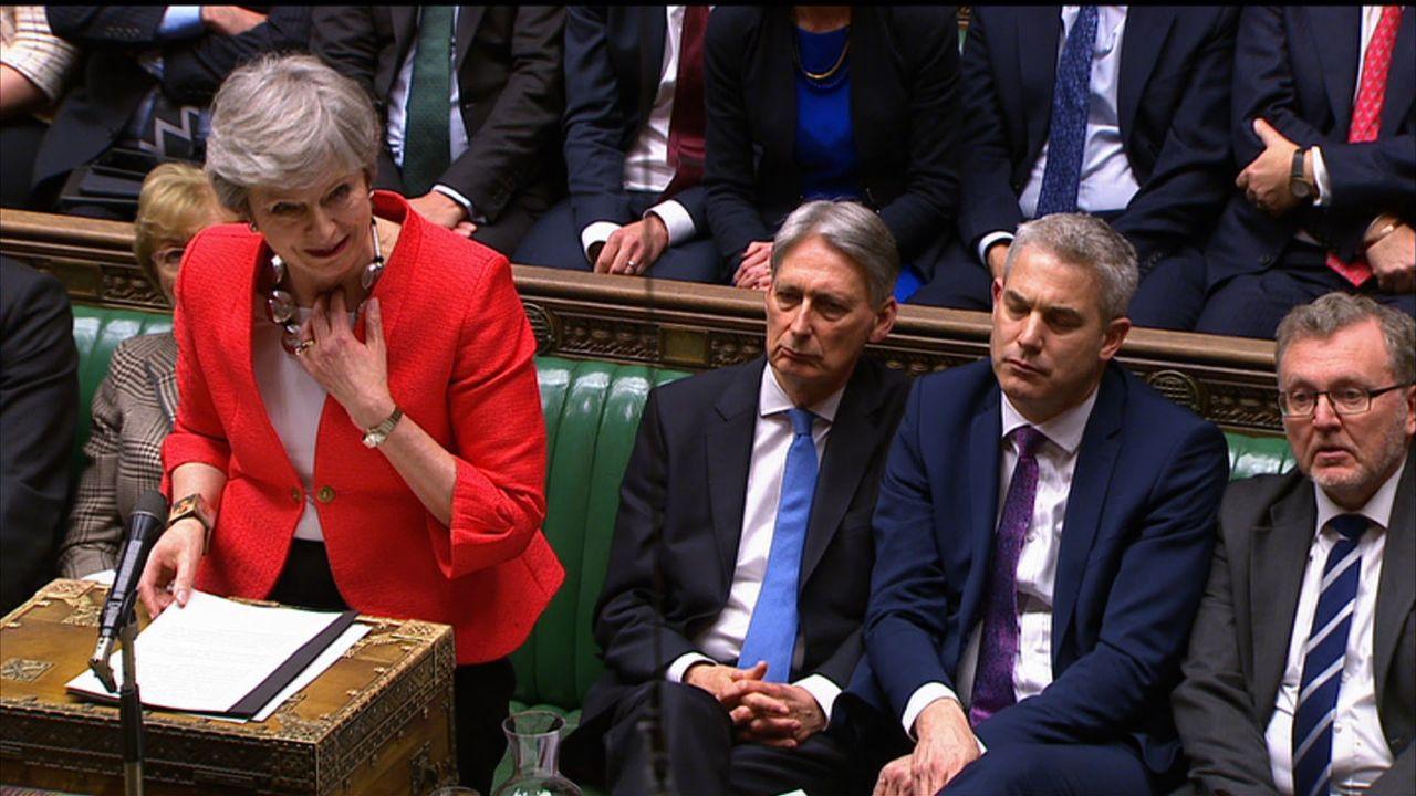 英國首相梅伊12日在國會演說,因為失聲而頻頻壓住喉嚨。法新社