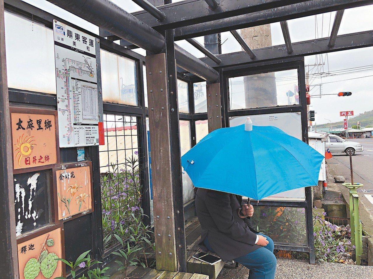 台東民眾在候車亭等公車,卻因候車亭失去遮雨功能,只能撐傘。 記者尤聰光/攝影