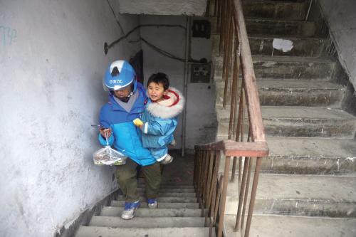 即使單手抱著女兒,李幫勇爬樓梯的速度也非常快。 嘉報集團全媒體視覺中心