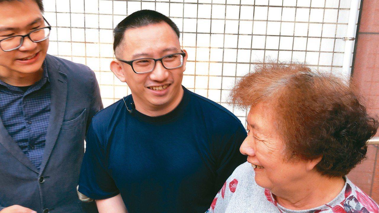 謝志宏(中)昨天傍晚重獲自由,開心與母親(右)牽手,並與協助他的夥伴一起高呼「謝...