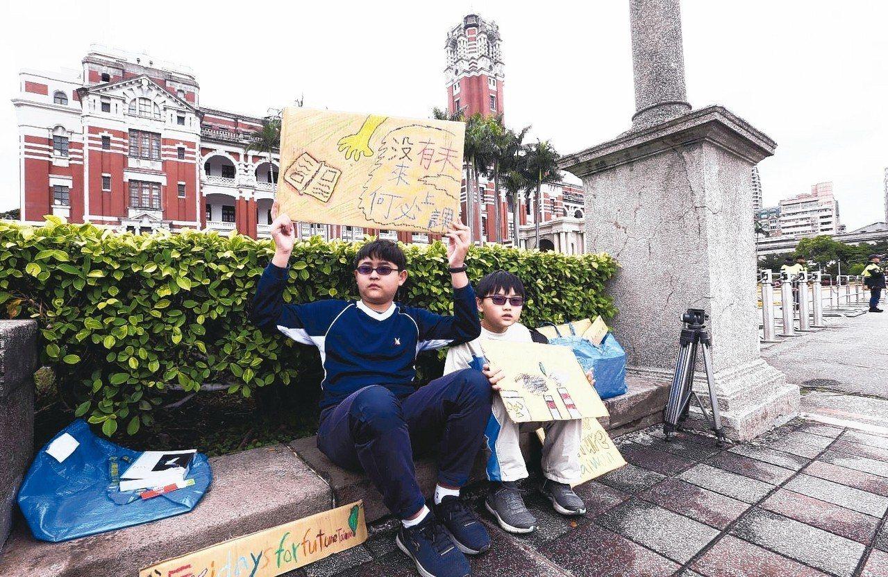 小學生楊子慶(左)與弟弟楊子瑩府前靜坐,手舉「沒有未來,何必上課」的自製標語。 ...