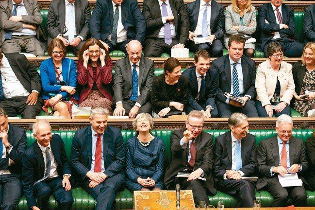英國國會14日以壓倒性票數通過脫歐至少延後三個月到6月30日,首相梅伊(前排右四...