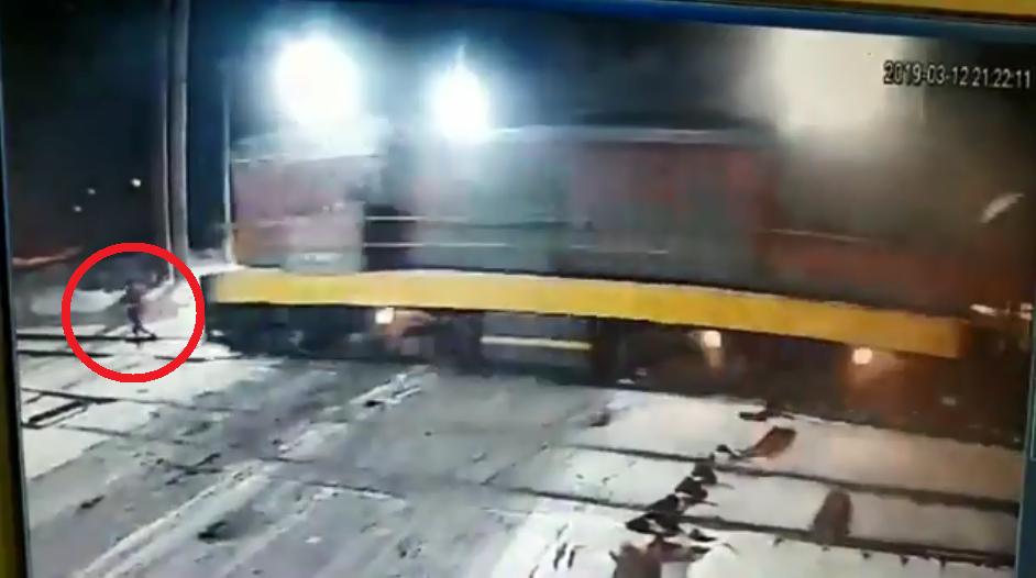 女子抱著男嬰穿越平交道,未注意火車駛來遭撞飛。圖擷自YouTube