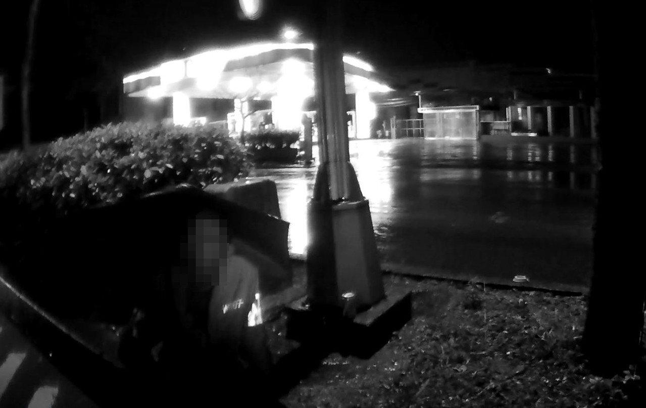 一名男子今天凌晨3時,冒著寒風細雨,撐傘呆坐車水馬龍的道路安全島上。警方擔心他安...