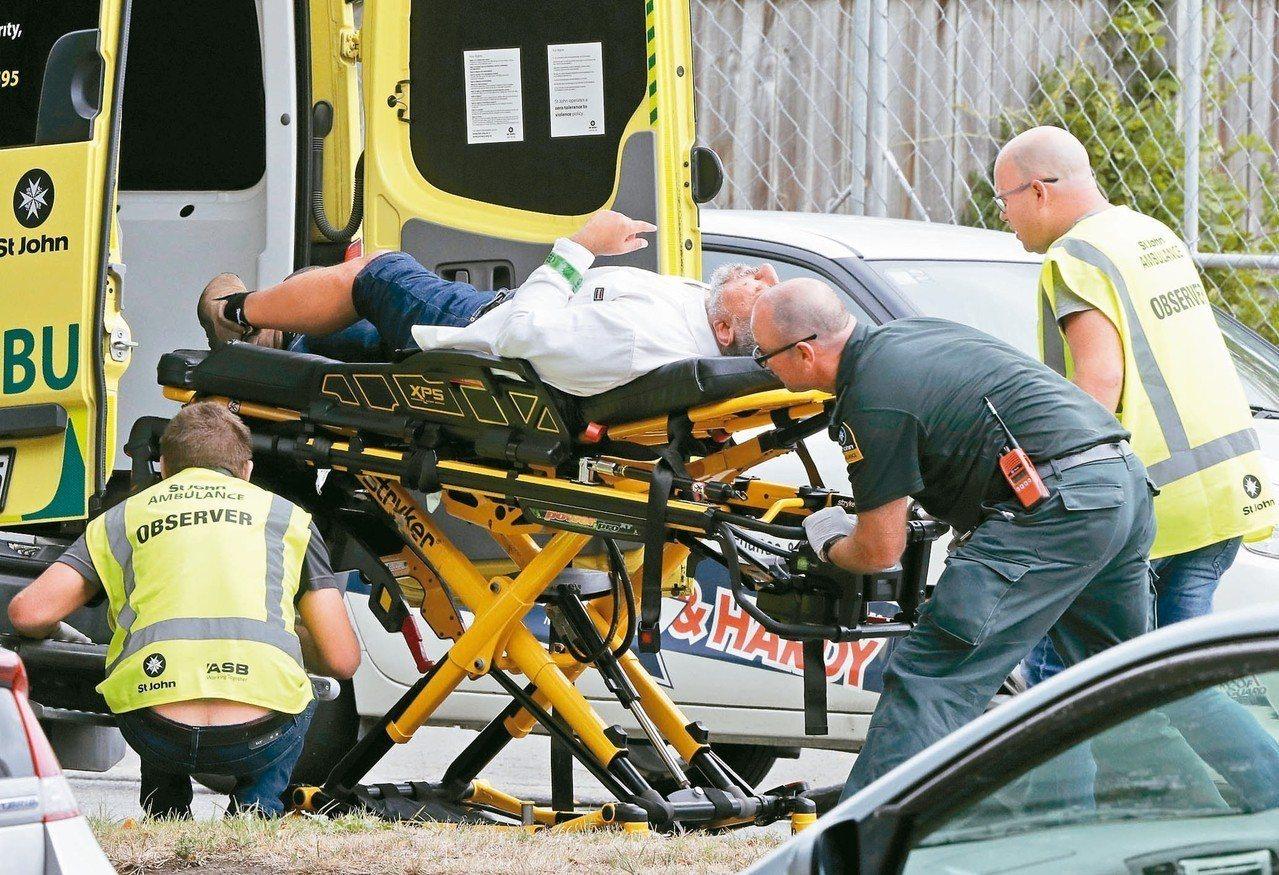 紐西蘭基督城十五日發生清真寺恐怖攻擊,救護人員將一名傷者送上救護車。 (美聯社)