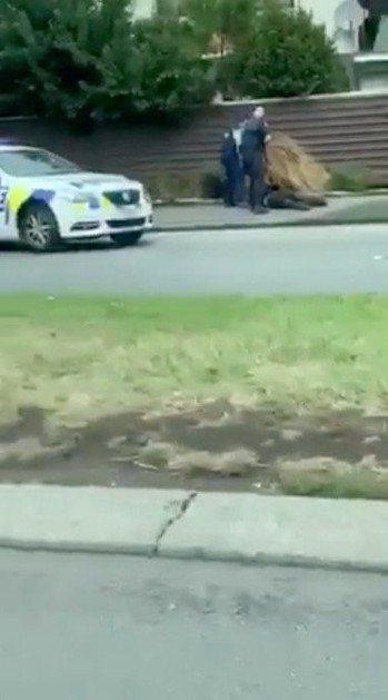 社群媒體傳送的影像顯示,紐西蘭警察持槍逮捕一名嫌犯(趴在地上)。 (路透)