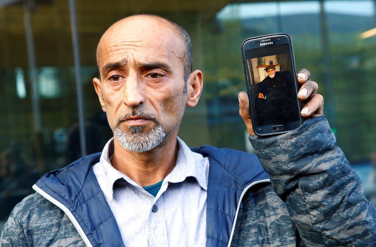 清真寺濫殺案一名死者之子,拿著手機展示他父親的照片。 (路透)