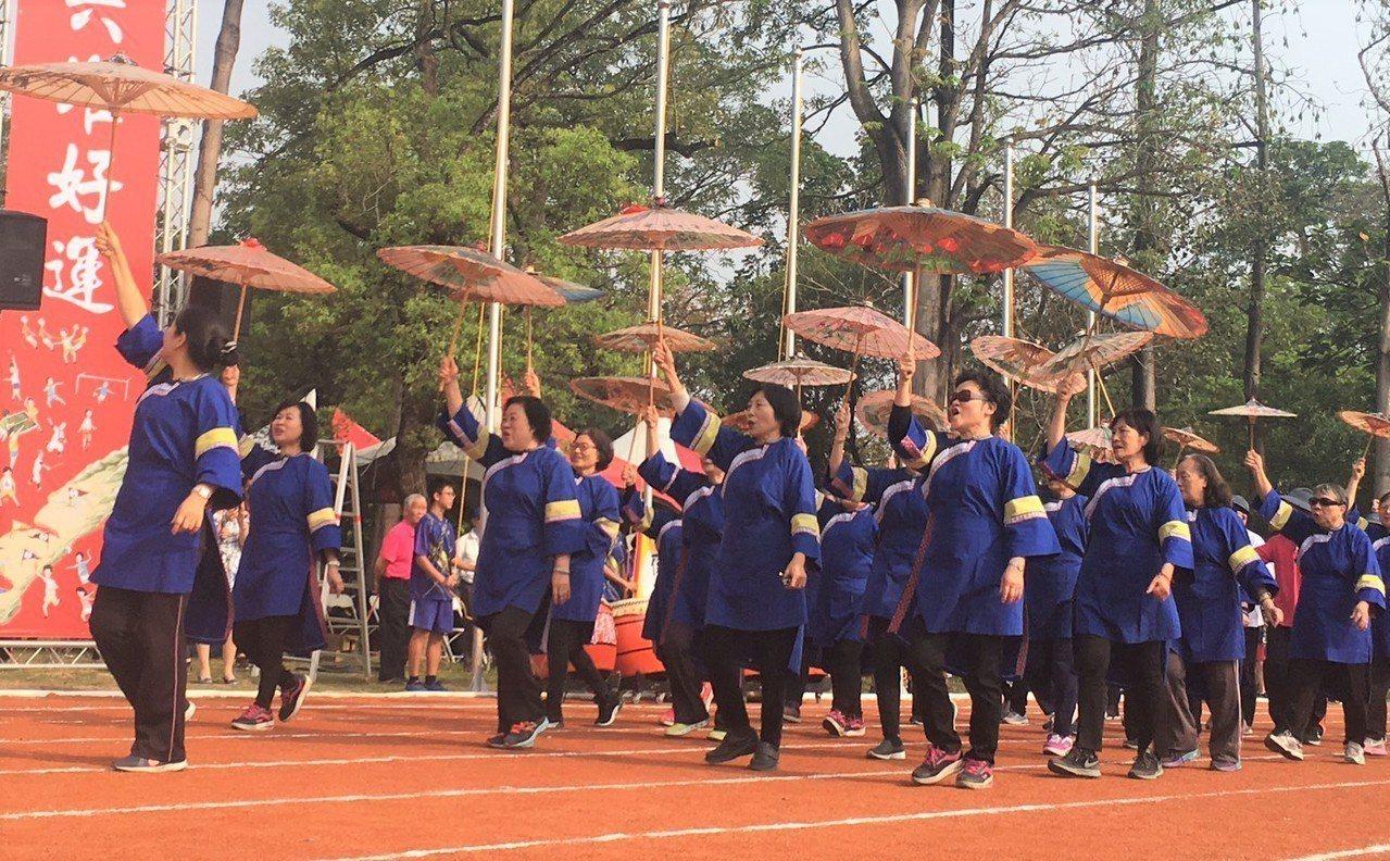 第54屆六堆運動會今天在屏東縣內埔國中登場,高雄美濃區隊以藍衫及美濃紙傘進場,展...