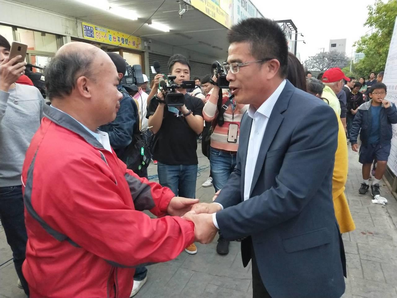 民進黨候選人黃振彥(右)承認敗選後,向競選總部外的支持者一一握手感謝,並表達努力...