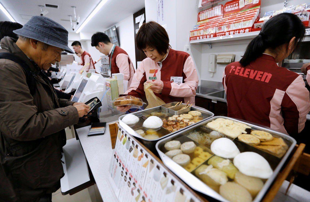日本東京一家7-eleven便利店內,店員為顧客結帳。 路透
