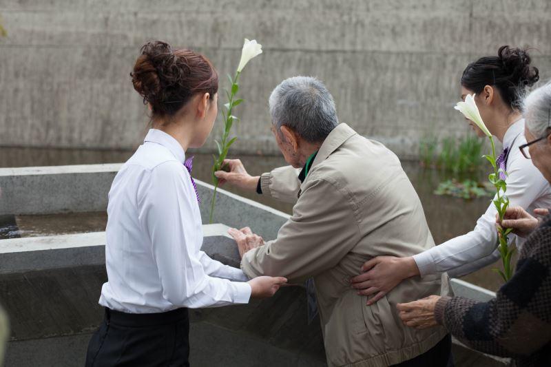 受難者許貴標前輩於紀念碑前獻花悼念難友們。圖/文化部提供