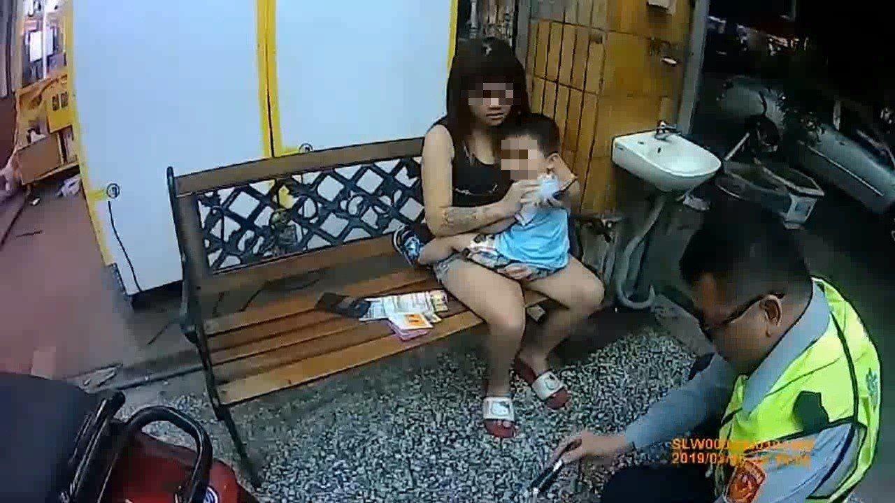 警方盤查朱女時,2歲兒子緊緊抱著她,但目光離不開員警。記者林伯驊/翻攝
