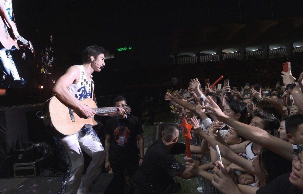 王力宏16日在大馬開唱,拿著吉他邊唱邊走下台。圖/宏聲提供