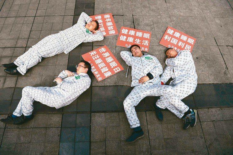為迎接2019年世界睡眠日,重慶鼾友會的成員身穿睡衣,手上拿著寫有「豬年睡如豬、...