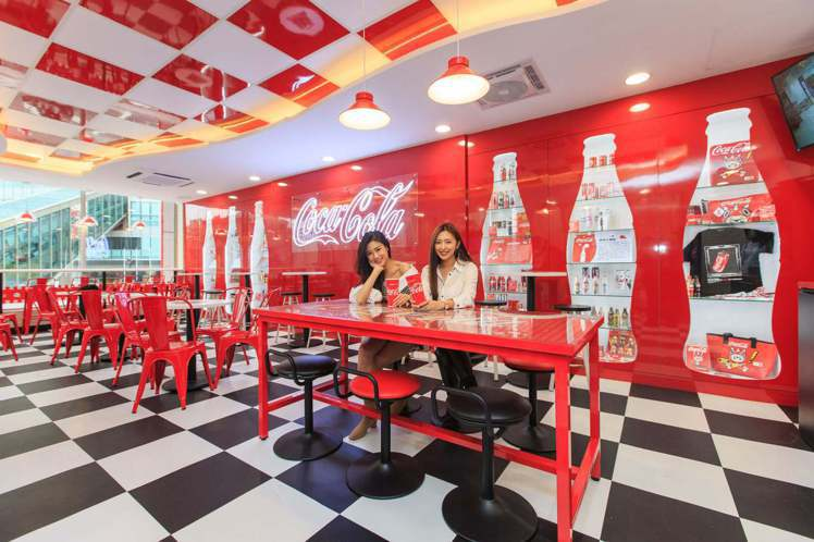 7-ELEVEN X「可口可樂」聯名店座位區有整面的「可口可樂曲線瓶」造型展示牆...