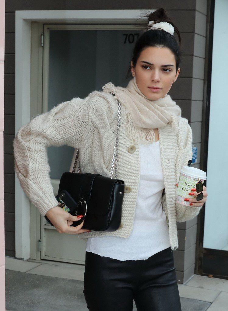 坎達爾珍娜以米色針織衫搭襯Amazone黑色素面荷篷包,氣質優雅。圖/取自spl...