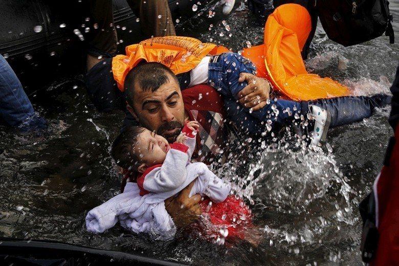 一位敘利亞難民父親抱著他的兩個孩子試圖上岸到希臘的列斯伏斯島。 圖/路透社