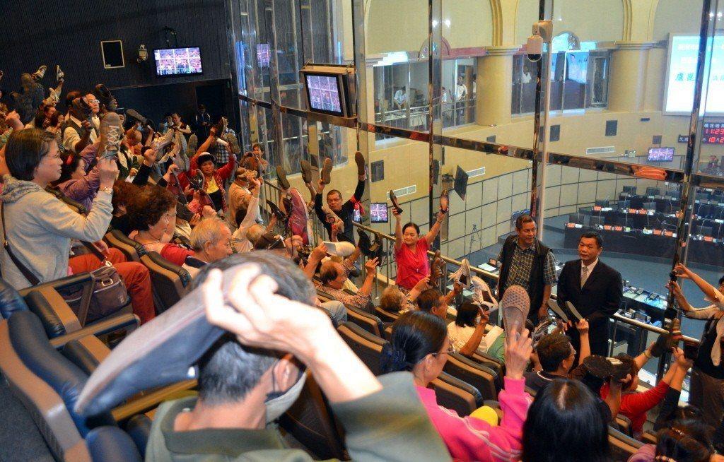 2013年台南沙卡里巴攤商拆除爭議,攤商於市議會旁聽席高舉鞋子作勢丟鞋抗議。 圖...