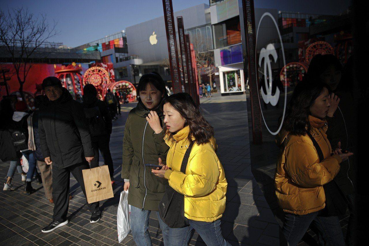 中國消費者在北京一處購物區逛街。 美聯社