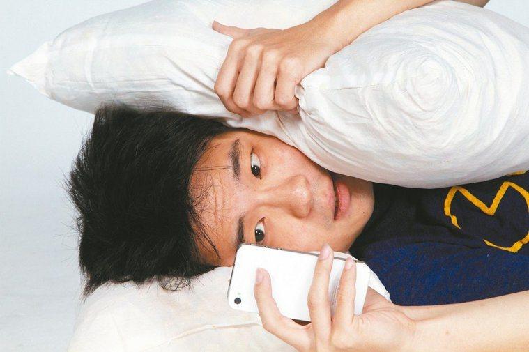 躺在床上熬夜玩手機。報系資料照