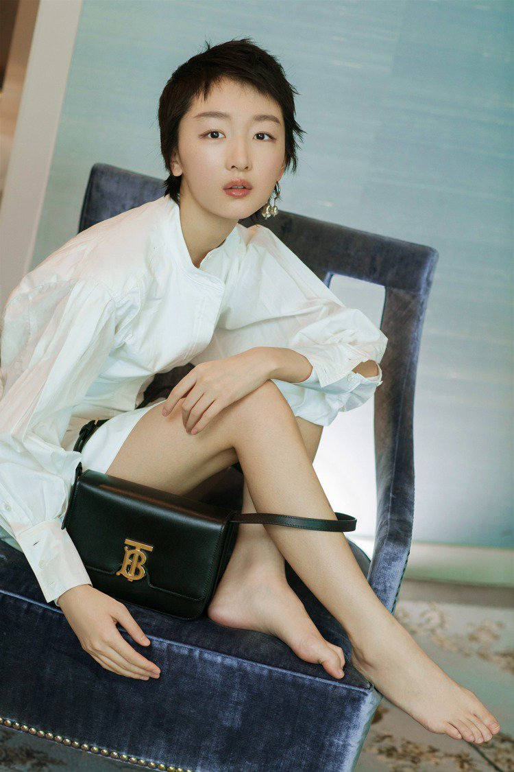 周冬雨以簡約的白色洋裝搭襯黑色款TB Bag。圖/BURBERRY提供