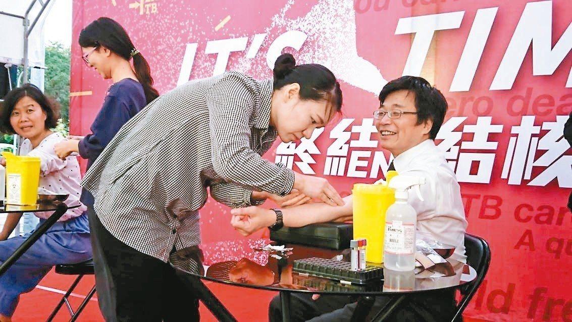 疾管署署長周志浩挽袖接受篩檢。 記者羅真/攝影
