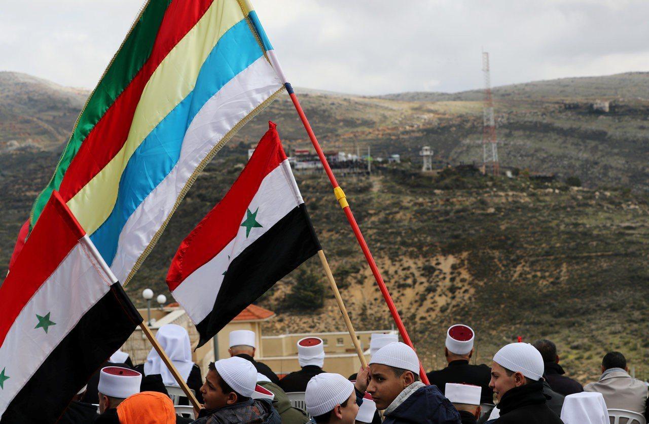戈蘭高地德魯茲族居民望著敘利亞,揮舞著敘利亞國旗和德魯茲旗幟。 (路透)