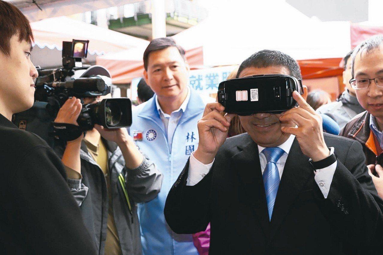 新北市長侯友宜(右)上午出席新北市就業服務處舉辦的就業博覽會,使用VR虛擬實境求...