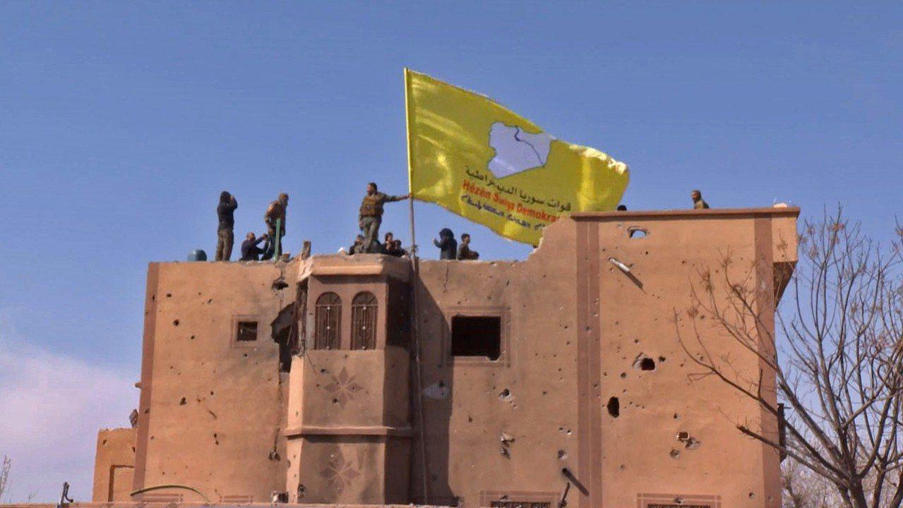 敘利亞民主力量23日在敘利亞東部清剿IS最後據點巴古斯村後,登上一棟建物樓頂,高...