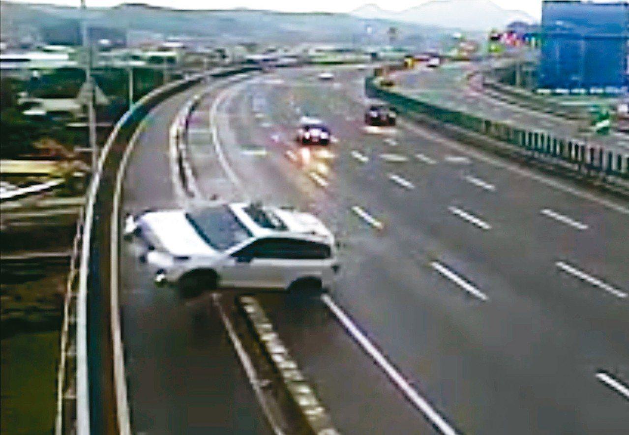 白色休旅車衝向道路右側,壓到汽、機車道分隔島,整輛車彈起。 記者林昭彰/翻攝
